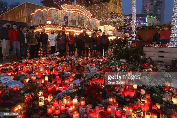 Visitors pause at a makeshift memorial at the reopened Breitscheidplatz Christmas market only a short distance from where three days ago a truck...