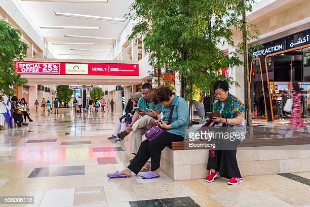 Visitors pause to check their mobile phones while shopping at the Yas Island Mall in Abu Dhabi United Arab Emirates on Monday May 30 2016 Abu Dhabi...