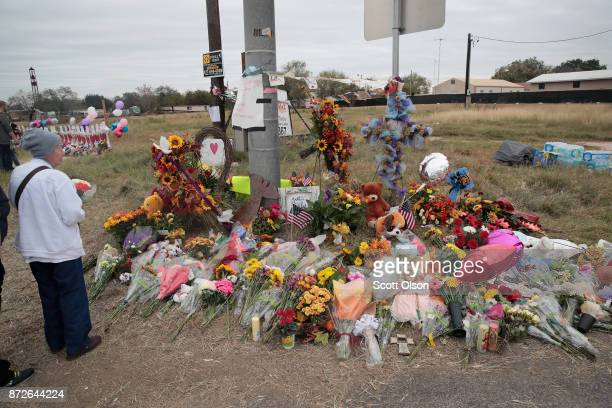 Visitors pay respects at a memorial where 26 crosses were placed to honor the 26 victims killed at the First Baptist Church of Sutherland Springs on...