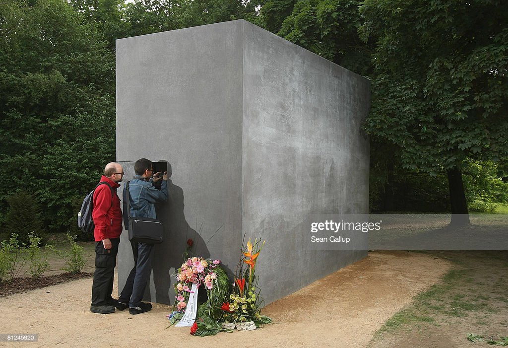 Visitors peek into the window of the newly-inaugurated memorial to homosexual victims of the Nazis on May 27, 2008 in Berlin, Germany. The memorial, a large stone with a window that looks onto an image of two men kissing, commemorates the tens of thousands of gays imprisoned by the Nazis, including the estimated 15,000 sent to concentration camps. The memorial stands in the Tiergarten park close the to Holocaust Memorial.
