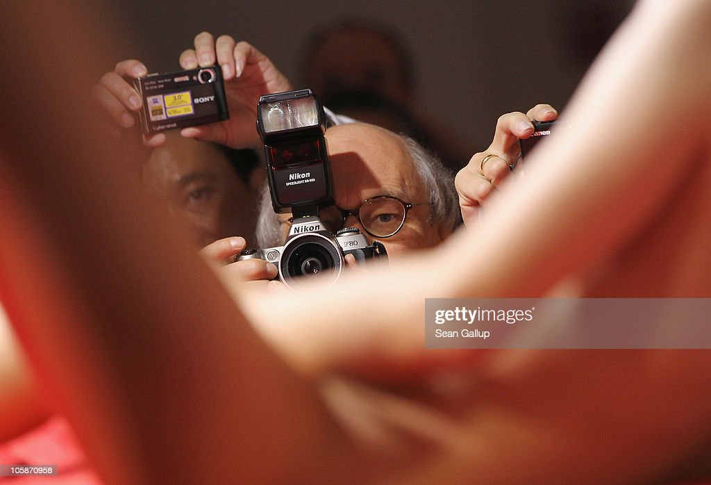 Visitors photograph a stripper performing on the industry professionals' day at the 2010 Venus Erotic Fair at Messe Berlin on October 21, 2010 in Berlin, Germany. The trade fair will be open from October 21 through 24.