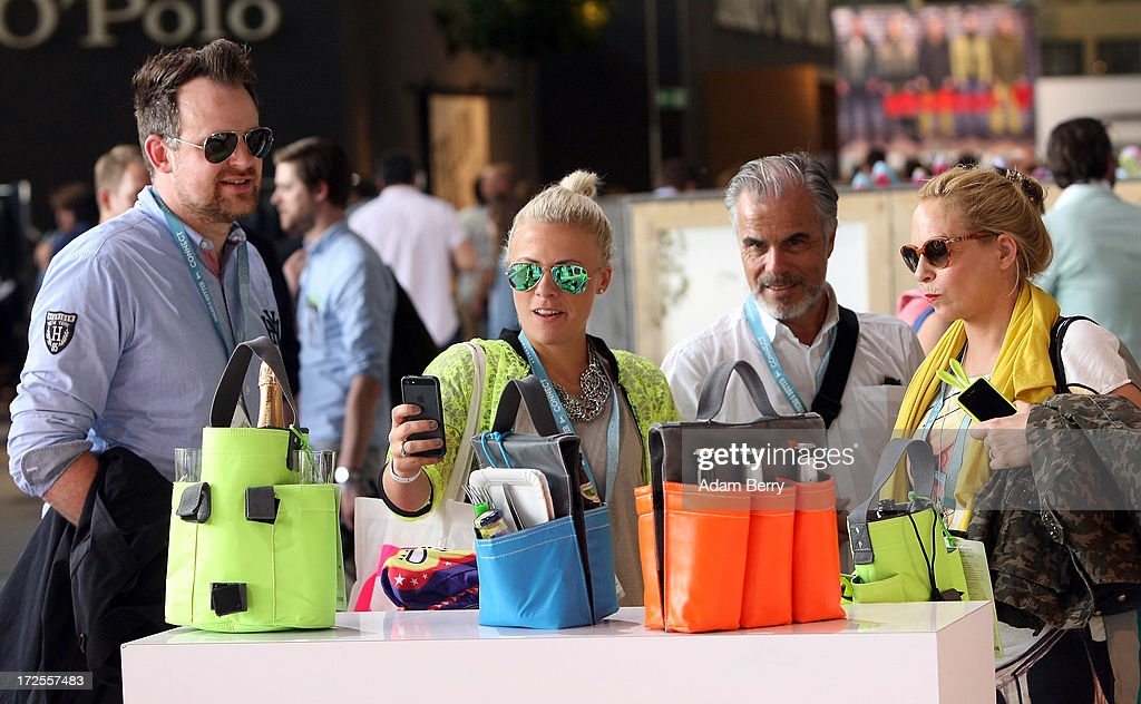 Visitors photograph bags designed to hold drinks during the Bread and Butter trade show at the former Tempelhof airport during Mercedes-Benz Fashion Week in Berlin on July 3, 2013 in Berlin, Germany.