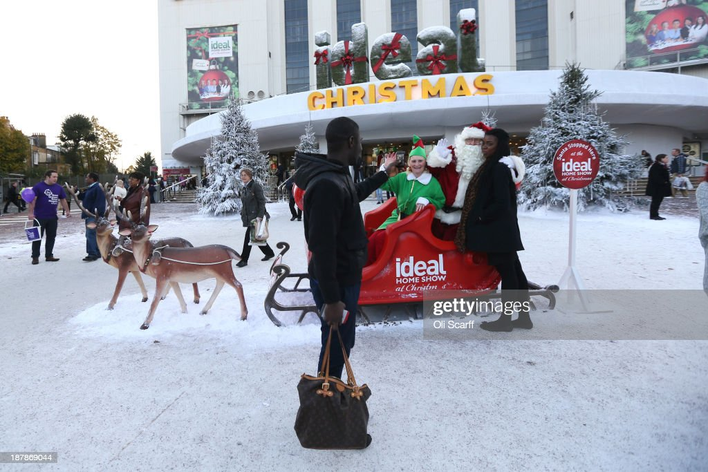 Visitors photograph each other outside the 'Ideal Home Show at Christmas' on November 13, 2013 in London, England. Over 80,000 visitors are expected to attend the 5 day event which showcases a range of gift ideas for Christmas in the Earls Court exhibition centre.