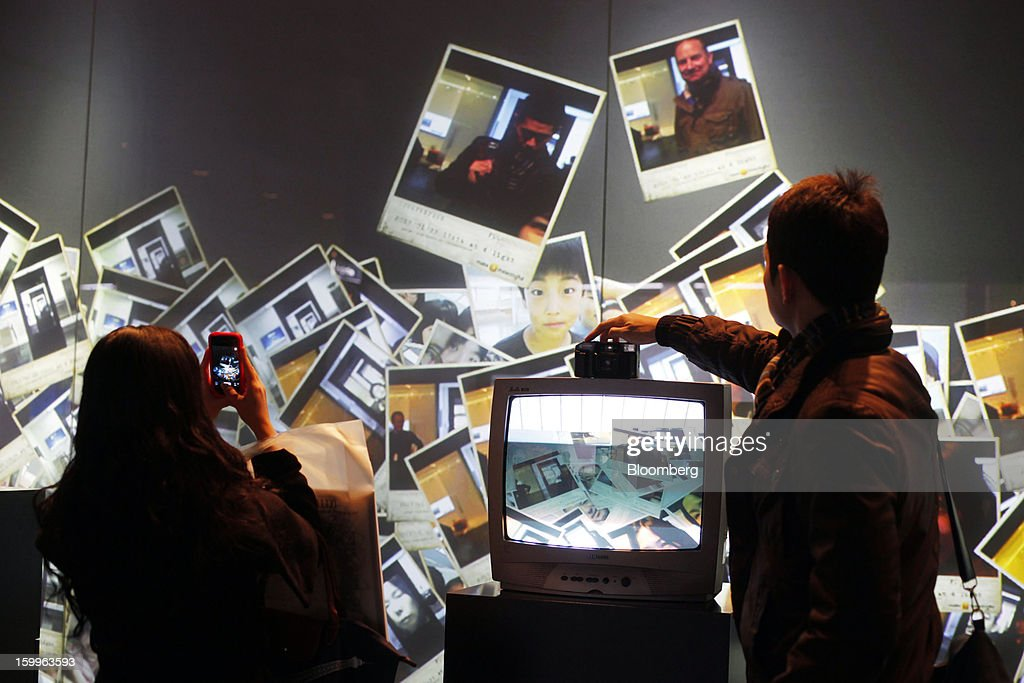 Visitors photograph, left, and try out the Capture Wall made up of 82 large format display (LFD) monitors at Samsung Electronics Co.'s Samsung d'light showroom and store in Seoul, South Korea, on Wednesday, Jan. 23, 2013. Samsung, in a preliminary statement of results on Jan. 8, reported an 89 percent jump in profit in the three months ended in December, boosted by its Galaxy line of smartphones. Photographer: Woohae Cho/Bloomberg via Getty Images