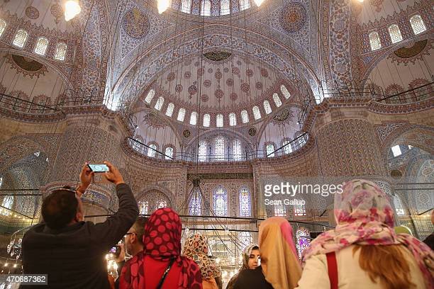 Visitors photograph the interior of the Blue Mosque on March 29 2015 in Istanbul Turkey Istanbul is a popular tourist destination