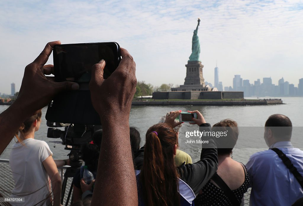 Visitors photograph the Statue of Liberty and the Manhattan skyline on May 27, 2016 in New York City. U.S. Secretary of Homeland Security Jeh Johnson visited nearby Ellis Island to administer the oath of citizenship to immigrants from 39 countries. The ceremony, held by U.S. Citizenship and Immigration Services (USCIS), was held in honor of Memorial Day and is one of 100 naturalization ceremonies held in U.S. national parks in celebration of the National Park Service's 100th anniversary.