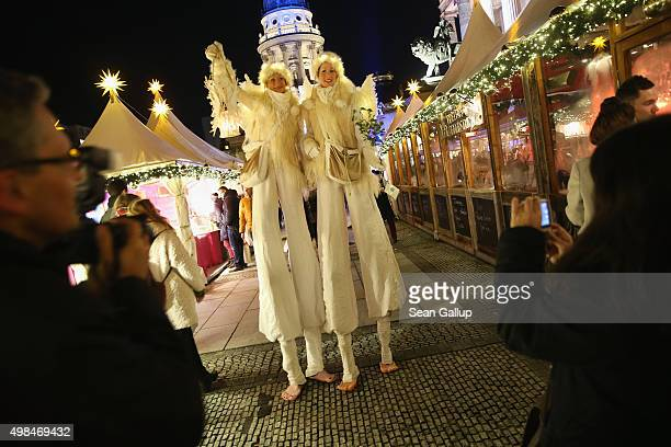 Visitors photograph two performers on stilts at the annual Christmas market at Gendarmenmarkt on its opening day on November 23 2015 in Berlin...