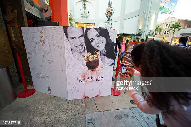 A visitors photographs a giant card congratulating Britain's Prince William and Kate Duchess of Cambridge on the birth of their baby boy outside the...
