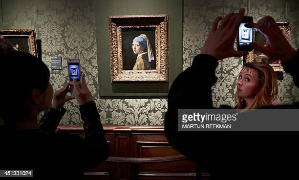 Visitors picture the painting of Johannes Vermeer's 'Girl with the Pearl Earring' during a special evening opening in the renewed Mauritshuis museum...