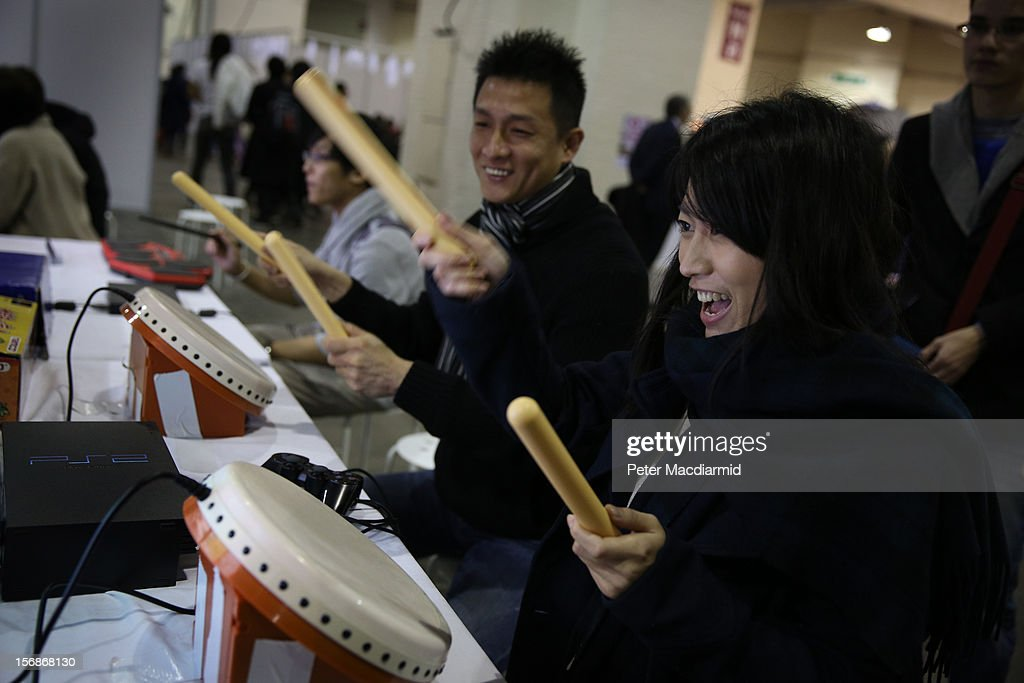 Visitors play a computerised drumming game at The Hyper Japan event at Earls Court on November 23, 2012 in London, England. The show is the UK's biggest Japanese Culture event, with stalls selling clothing and artwork. live music, Japanese food and computer gaming areas are also on show. Many attendees dress up as anime characters or in the lolita fashion widespread in Japan.