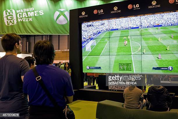 Visitors play a FIFA football video game during the first day of the Madrid Games Week dedicated to professionals in Madrid on October 16 2014 The...
