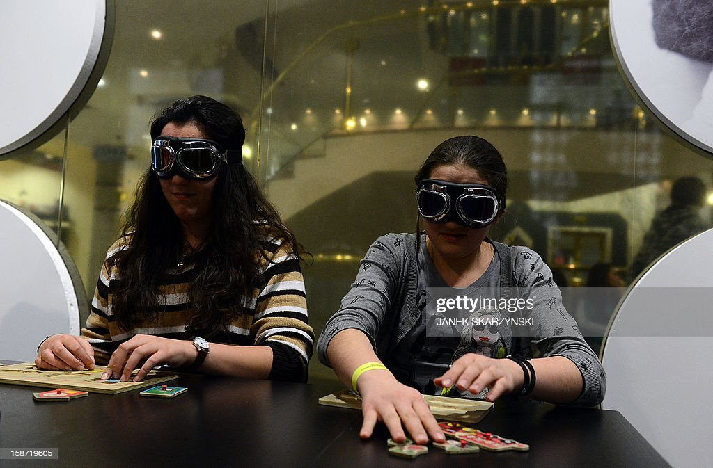 Visitors play a game that stimulates the visitors' senses and reveals the tools that the blind use in their daily lifes in the 'invisible exhibition' on December 18, 2012 in Warsaw.