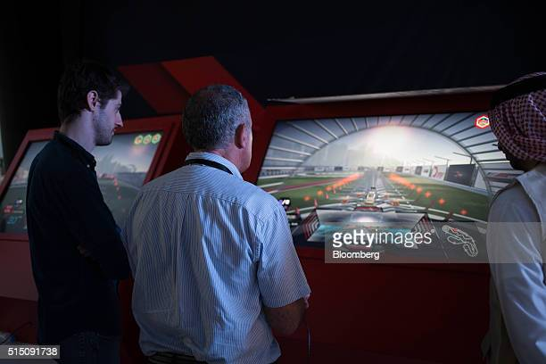 Visitors play a virtual reality game that simulates racing a drone along the track designed for finals at the World Drone Prix drone racing...