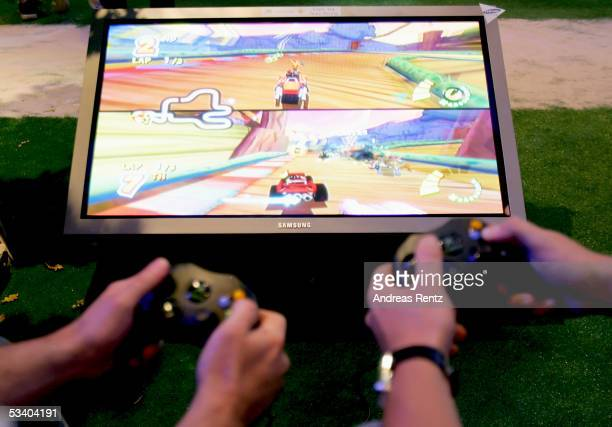 Visitors play at the Microsoft 'XBOX 360' stand at a Computer Gaming Convention on August 18 2005 in Leipzig Germany The convention is Germany's...