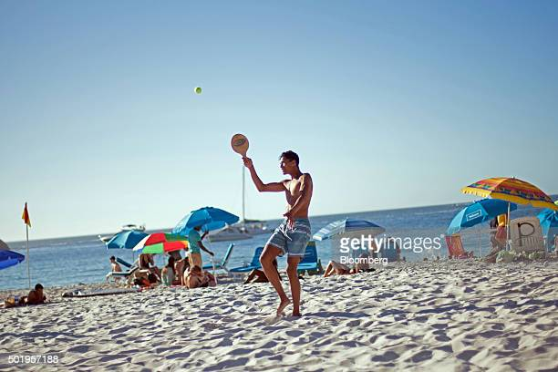 Visitors play beach tennis and sit beneath parasols on Lagoon beach in Cape Town South Africa on Friday Dec 18 2015 The currency's slump has added to...