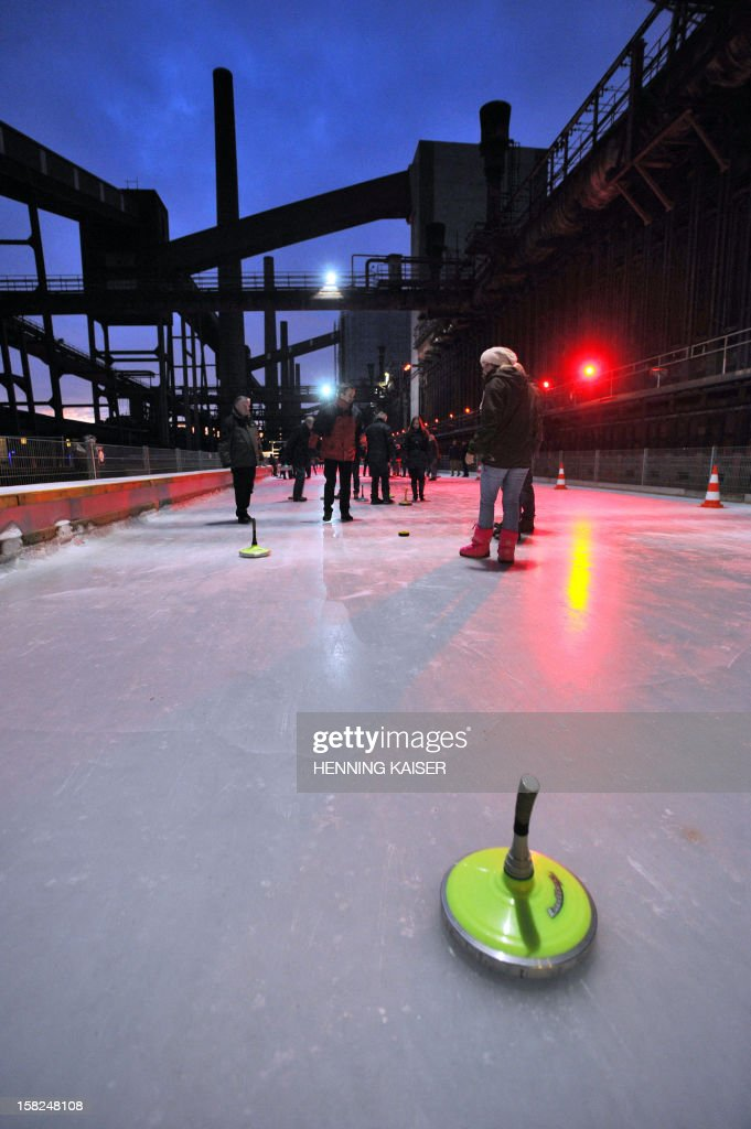 Visitors play curling on an outdoor rink at the former Zeche Zollverein coal mining plant in Essen, western Germany, on December 11, 2012. Mining activities at Zeche Zollverein started in 1851 and were closed down in 1986. Since 2001, the former industrial site is inscribed at the UNESCO World Heritage Sites list.