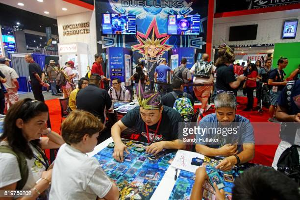 Visitors play Duel Links at their booth during Comic Con International on July 20 2017 in San Diego California Comic Con International is North...