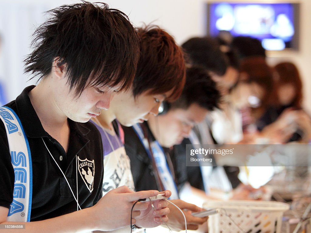 Visitors play game on Apple Inc. iPhones at the Tokyo Game Show 2012 at Makuhari Messe in Chiba, Japan, on Thursday, Sept. 20, 2012. The show will be held through Sept. 23. Photographer: Tomohiro Ohsumi/Bloomberg via Getty Images