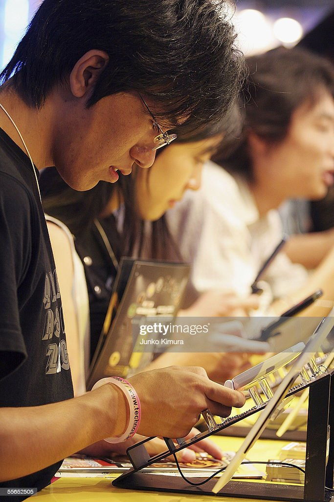 Visitors play games on mobile phones during the Tokyo Game Show 2005 on September 16, 2005 in Chiba, Japan. The show which takes place from September 16 for 3 days is expected to attract 150,000 visitors.