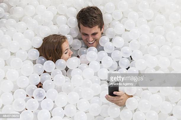 Visitors play in 'The Beach' at the National Building Museum on August 19 2015 'The Beach' is an interactive installation meant to mimic a beach but...