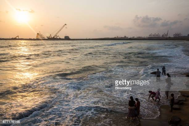 Visitors play in the sea at Galle Face Green as the construction site of the Colombo Port City development stands in the background in Colombo Sri...