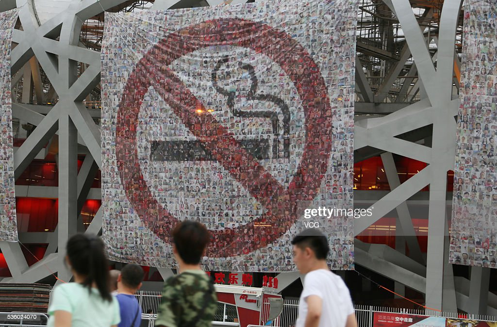 Visitors play near the Birds Nest where placards were hung to advocate no smoking on World No Tobacco Day on May 31, 2016 in Beijing, China. The World No Tobacco Day falls on May 31 each year.