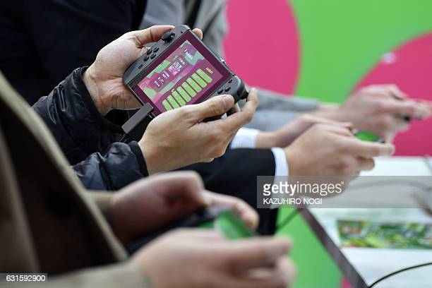 Visitors play Nintendo's new video game console Switch during its presentation in Tokyo on January 13 2017 Nintendo on January 13 unveiled its new...