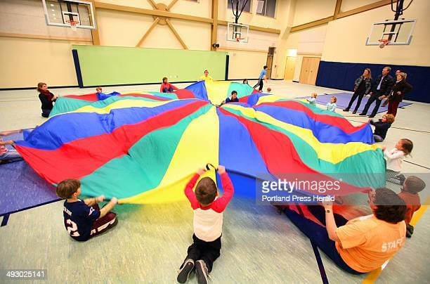 Visitors play parachute games in the gym during the open house of the new Ocean Avenue Elementary School in Portland on February 10 2011