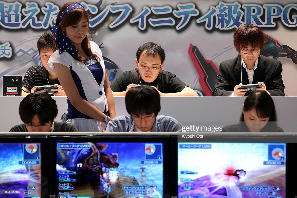 Visitors play Sega Corp.'s 'Phantasy Star Portable 2 Infinity' on Sony Computer Entertainment Inc.'s PlayStation Portable (PSP) handheld game consoles while a booth assitant looks on during the Tokyo Game Show 2010 at Makuhari Messe on September 16, 2010 in Chiba, Japan. The computer and video game convention, which will be held until September 19, features exhibitions of upcoming game software and hardware from 194 companies and organizations to draw business visitors and the general public.