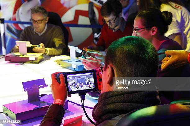 Visitors play the ' Mario Kart 8 deluxe' on a Nintendo Switch games console during the new console's unveiling by Nintendo Co on January 13 2017 in...