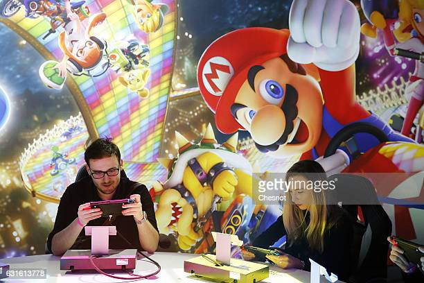 Visitors play the 'Mario Kart 8 Deluxe' video game on a Nintendo Switch games console during the new console's unveiling by Nintendo Co on January 13...