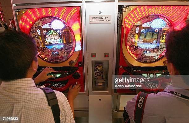 Visitors play with Abilit Republic's Japanese pinball at the company's booth at the Tokyo Game Show 2006 on September 22 2006 in Chiba Prefecture...
