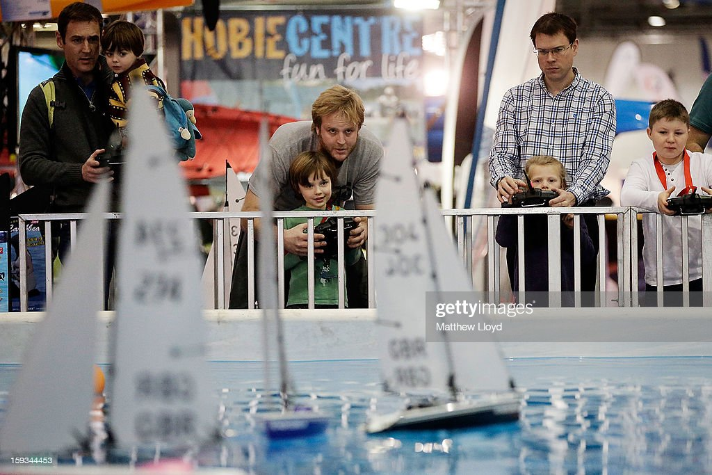 Visitors play with remote controlled boats on an indoor pool at the 2013 London Boat Show, held at the eXcel centre, on January 12, 2013 in London, England. Until the 20th of January the London Boat Show will showcase, demonstrate and sell maritime equipment ranging from luxury yachts to dinghies.