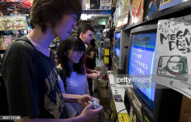 Visitors plays a video game on the Nintendo Co Super Nintendo Entertainment System console at the Super Potato video game store in the Akihabara...