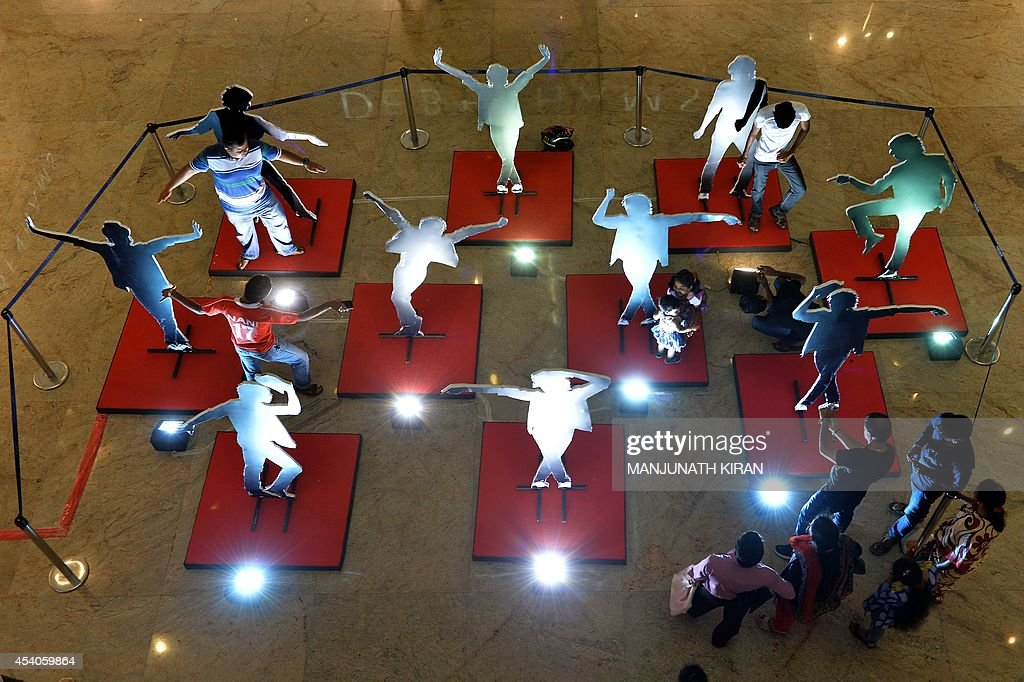 Visitors pose and take photographs in front of life-sized dance pose silhouettes of the late US pop star Michael Jackson at a commemorative exhibition, set up at the mall as part of birthday celebrations for the late music icon, in Bangalore on August 23, 2014. Fans of the lengendary pop star Michael Jackson, who passed away in 2009, are gearing up to celebrate what would have been his 56th birthday on August 29. AFP PHOTO/Manjunath KIRAN