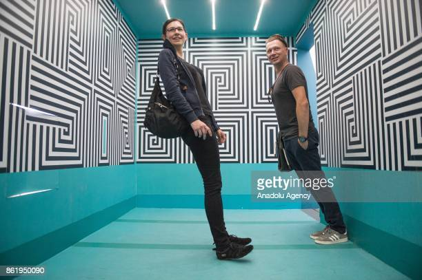 Visitors pose for a photo inside of the Anti Gravity room an exhibition part of the Museum of Illusions in Vienna Austria on October 16 2017 The...