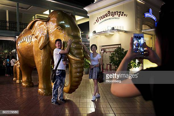Visitors pose for a photograph next to a statue of an elephant at Asiatique The Riverfront openair mall in Bangkok Thailand on Friday Dec 18 2015...