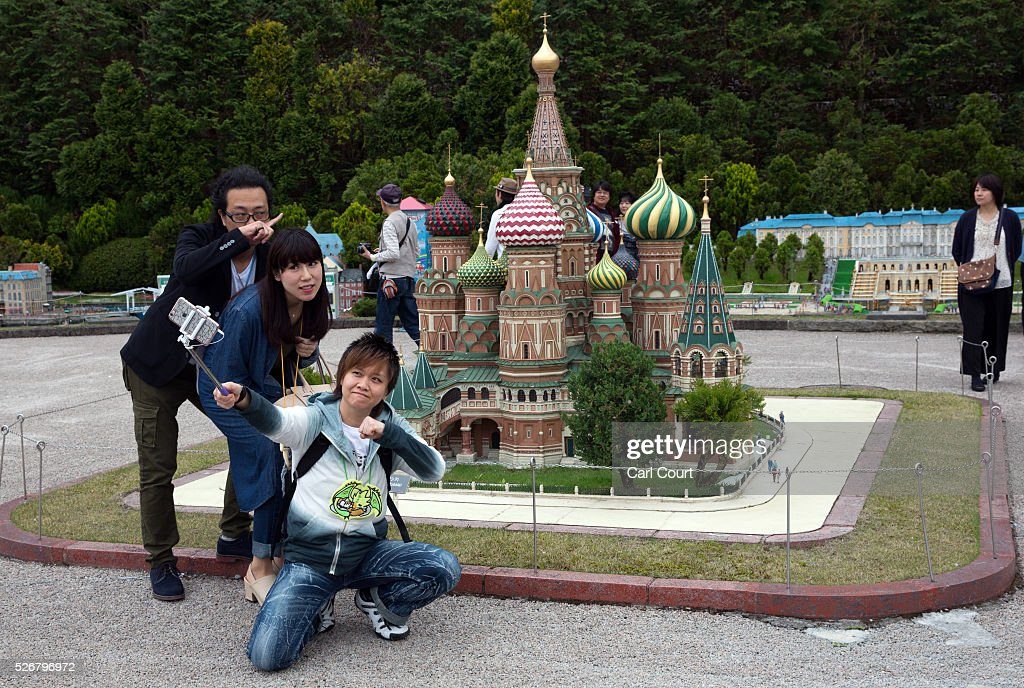 Visitors pose for a photograph next to Saint Basil's Cathedral at Tobu World Square theme park on May 01, 2016 in Nikko, Japan. Tobu World Square contains over a hundred 1:25 scale models of famous buildings, including World Heritage Sites, complete with 140,000 1:25 miniature people and receives visitors from around the world.