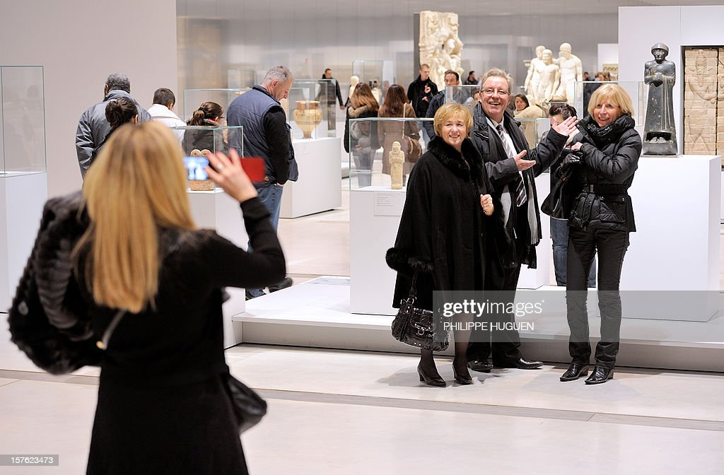 Visitors pose for a picture at the Louvre Museum on the first day of its opening to the public, on December 4, 2012 in Lens, northern France. The Louvre museum opened a new satellite branch among the slag heaps of a former mining town Tuesday in a bid to bring high culture and visitors to one of France's poorest areas. Greeted by a group of former miners in overalls and hardhats, President Francois Hollande inaugurated today the Japanese-designed glass and polished-aluminium branch of the Louvre in the northern city of Lens. The 150 million euro ($196 million) project was 60 percent financed by regional authorities in the Nord-Pas-De-Calais region, on the English Channel and the border with Belgium. AFP PHOTO PHILIPPE HUGUEN