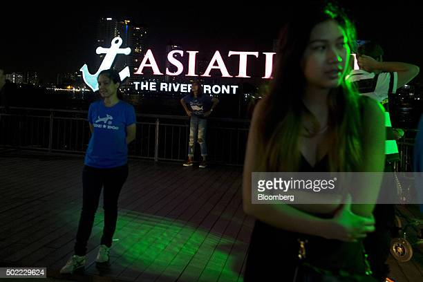 Visitors pose for photographs in front of an illuminated sign for Asiatique The Riverfront openair mall in Bangkok Thailand on Friday Dec 18 2015...