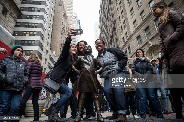 Visitors pose for photos with the 'Fearless Girl' statue March 27 2017 in New York City New York City Mayor Bill De Blasio announced that the popular...