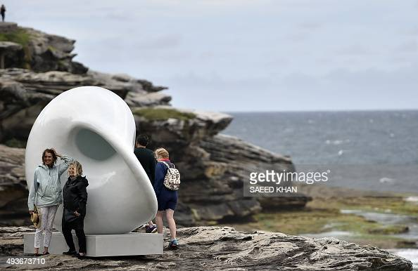 Visitors pose for pictures in front of a sculpture by artists Arissara Reed and Davin Nurima at the 'Sculpture by the Sea' exhibition which runs...