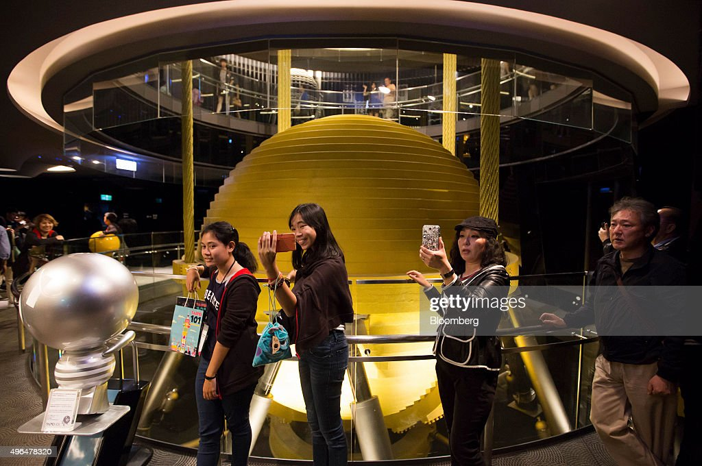 Visitors pose for selfie photographs in front of a tuned mass damper in the Taipei 101 building in Taipei Taiwan on Sunday Nov 8 2015 In his meeting...