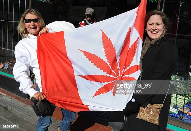 Visitors pose in front of a flag similiar to the Canadian one but showing a cannabis plant instead of a maple leaf at a store in Eastside Vancouver...