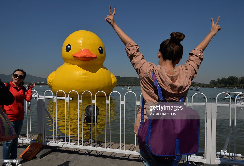 Visitors pose in front of an 18-metre tall inflatable duck beside a Chinese pagoda after its move to the historic Summer Palace in Beijing on September 26, 2013. The duck designed by Dutch artist Florentijn Hofman is to be displayed at Beijing's Garden Expo Park and the Summer Palace, from September to October as part of a world tour of 13 cities across 10 countries. AFP PHOTO / Mark RALSTON