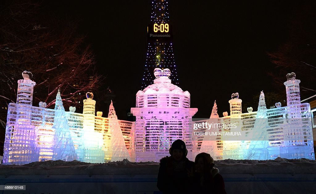 Visitors pose in front of an ice sculpture of the Palace of the Heart during the 65th annual Sapporo Snow Festival in Sapporo on February 5, 2014. The week-long festival started with a total of 198 snow statues on display. AFP PHOTO / TOSHIFUMI KITAMURA