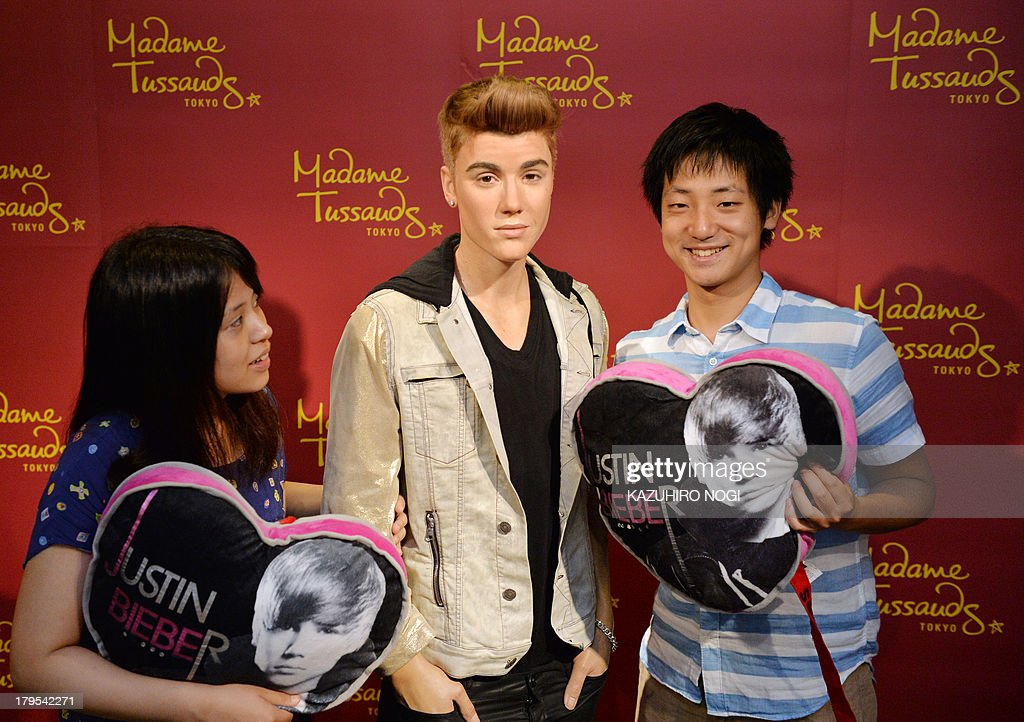 Visitors pose with a life-size wax figure of Canadian pop musician Justin Bieber at Tokyo's Madame Tussaud wax museum on September 5, 2013. The newest figure of Justin Bieber will be displayed during a limited run exhibition here September 7 to October 20, to commemorate Bieber's visit to Japan for the first time in two years.