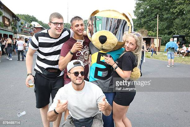 Visitors pose with BreuniBaer mascot of Breuninger at the ParookaVille Festival on July 15 2016 in Weeze Germany