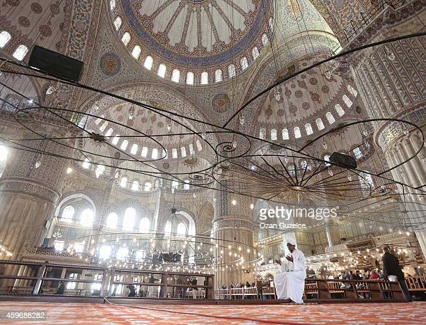 Visitors pray in the Blue Mosque before Pope Francis visit in central Istanbul on November 28 2014 Pope Francis arrived in Turkey on Friday at a...