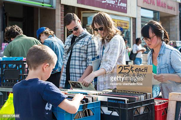 PORTUGAL TORONTO ONTARIO CANADA Visitors purchasing vinyl records kept on sale at Little Portugal festival which is a bustling street festival with...